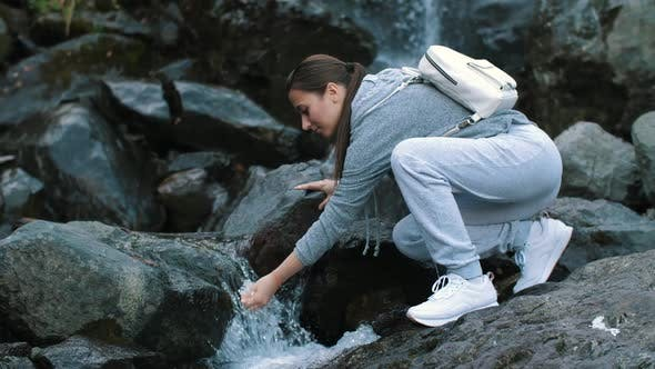 Woman Drinking a Freshwater Stream
