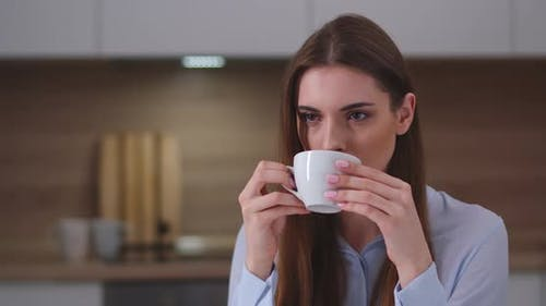 Young Beautiful Girl Sitting in the Kitchen and Drinking Coffee, Portrait, Day Off at Home