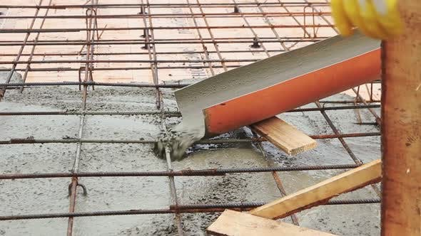 Pouring concrete mixture to the reinforcing mesh and a house foundation