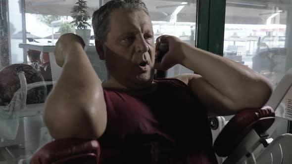 Mature Man Working on Weight-Lifting Machine