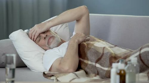Old Person Sleeping in Bed and Suffering From Terrible Headache, Illness