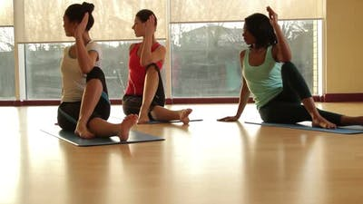 Yoga students practicing yoga in yoga studio