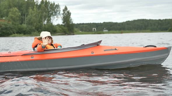 Thumbnail for Child in Vest Waves Hand To Camera in Kayak Sailing on Lake