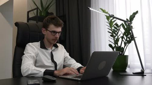 Young handsome man in eyeglasses and shirt is sitting at home office workplace, opening laptop