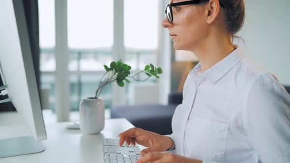 Thumbnail for Woman with Glasses Typing on a Computer Keyboard. Concept of Remote Work.