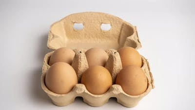 Eggs appear and disappear in Cardboard egg box on white background. Stop motion animation