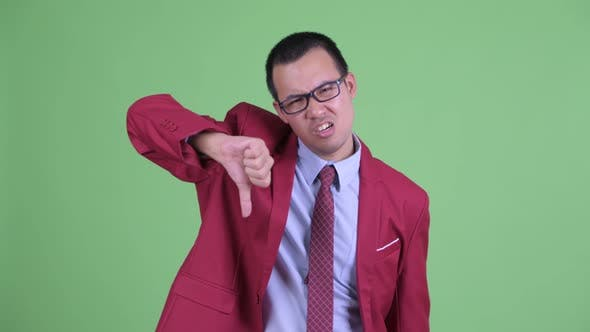 Thumbnail for Angry Asian Businessman with Eyeglasses Giving Thumbs Down