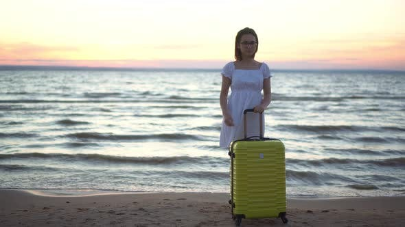 Thumbnail for Young Woman with a Yellow Suitcase on the Beach By the Sea. Girl in a White Dress By the Sea at