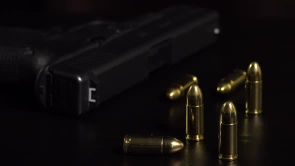 Thumbnail for Closeup on Bullets and a Gun on a Black Table