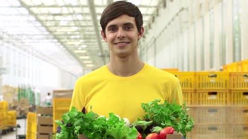 Man Volunteer posiert mit einer Kiste Gemüse in seinen Händen bei Agro Company Spbd