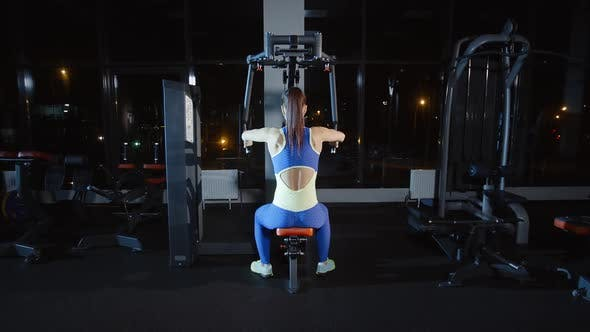 Thumbnail for Attractive Woman Athlete Doing Workout Training Hands Chest and Her Back on Weights Exercise Machine