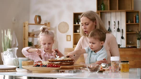 Thumbnail for Loving Mom Making Layered Berry Cake with Young Kids