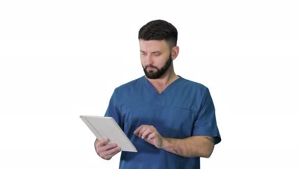 Confident Concentrated Focused Surgeon Using Digital Tablet on White Background