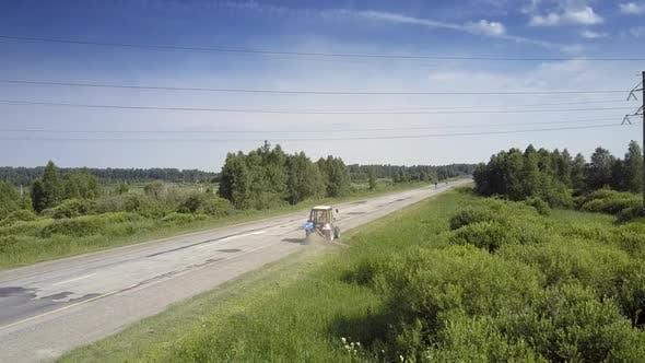 Tractor Mows Grass Along Wayside Under High Voltage Line