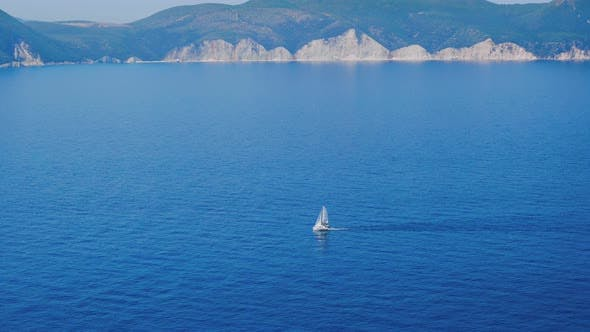 Thumbnail for Alone White Boat Sailing in the Deep Blue Mediterranean Sea. Picturesque Contours of Greek Coastlie