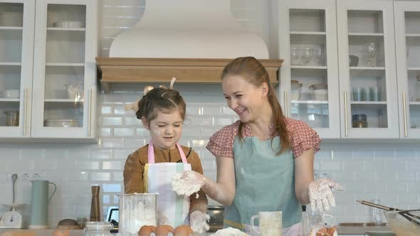 Thumbnail for Cheerful Girl and Mommy Throw Flour Making Dough in Kitchen