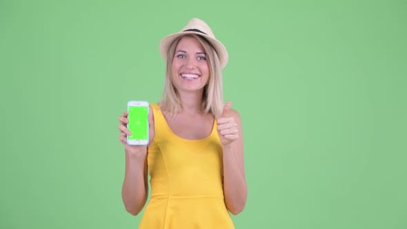 Thumbnail for Happy Young Blonde Tourist Woman Showing Phone and Giving Thumbs Up