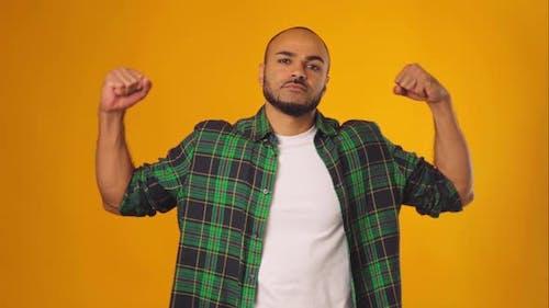 Afroamerikaner Mann in Freizeithemd zeigt seine starken Hände vor gelbem Hintergrund