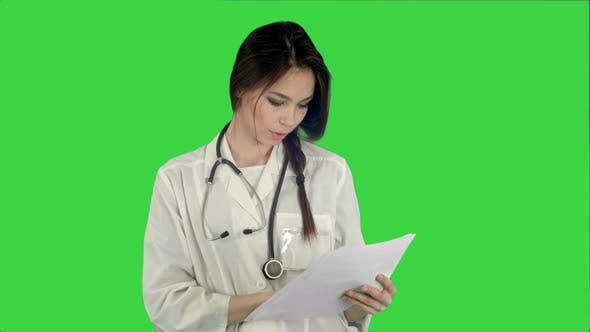 Thumbnail for Young Female Doctor Reading Patient Medical History Forms on a Green Screen