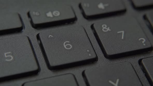 The Finger Presses a Button with a Number on the Keyboard