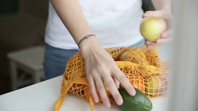 Reusable Minimalist Grocery Bag with Fruits and Vegetables on the Kitchen on White Table Iroi