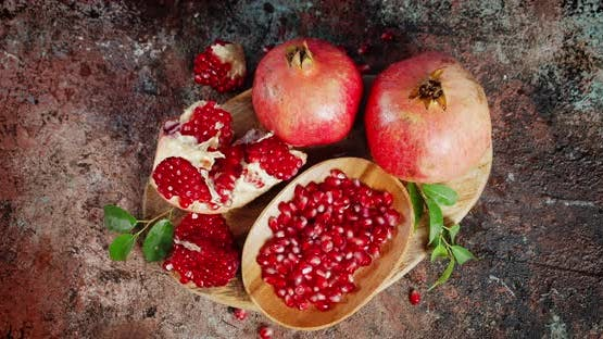 Grains of Ripe Pomegranate on Wooden Plate Rotate Slowly