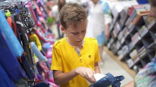 Boy choosing school stationery. Young boy choosing school supplies in stationery shop