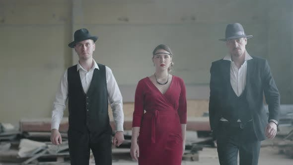 Thumbnail for Two Confident Men in Hats and Suits and Woman in Red Dress Walking Towards the Camera
