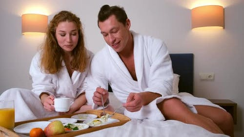 Man and Woman in Bathrobes Having a Breakfast Together in Bed in Hotel Room