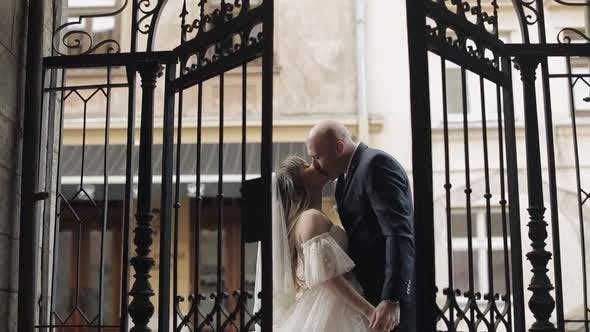 Thumbnail for Newlyweds at the Old Gate Making a Kiss, Bride and Groom, Kiss, Wedding