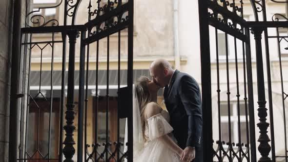 Thumbnail for Brautpaar am alten Tor machen einen Kuss, Braut und Bräutigam, Kuss, Hochzeit