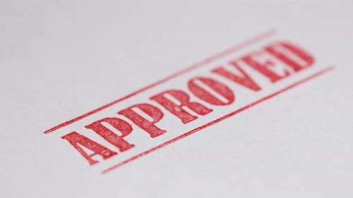 A Stamp Approved is Placed on a Sheet of White Paper Closeup