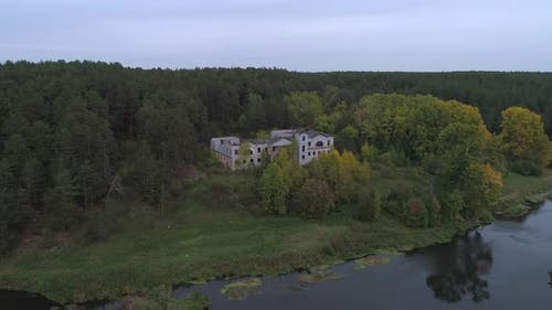 Big abandoned house in the woods on the banks of the river
