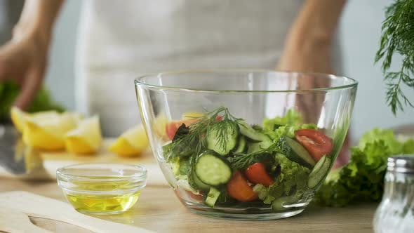 Thumbnail for Closeup of Female Chef Hands Squeezing Fresh Lemon Juice Into Bowl with Salad