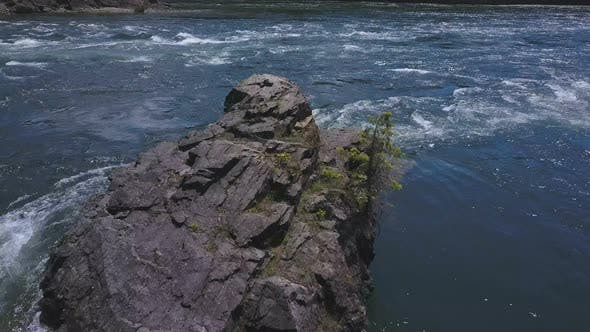 Thumbnail for Aerial Drone Traveling Above Flowing Water With Small Rocky Island Below 2