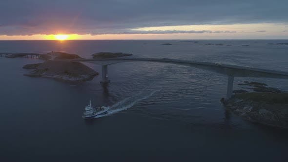 Thumbnail for Atlantic Ocean Road in Norway at Sunset. Ship Is Passing Under Storseisundet Bridge. Aerial View