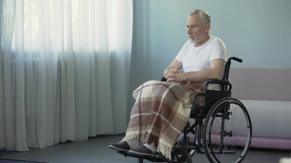 Cover Image for Handicapped Pensioner Sitting in Wheelchair and Thinking About Life Sadness