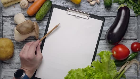 Faceless Cook with Pencil Pointing at List of Ingredients