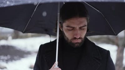 Sad Man Under Umbrella at the Funeral