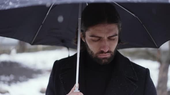 Sad Man Under Umbrella at the Funeral