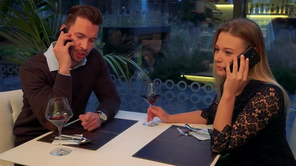 Thumbnail for A Man and a Woman Sit at a Table in a Restaurant and Talk on Their Smartphones