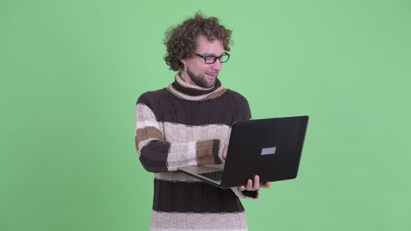Thumbnail for Happy Young Bearded Man Thinking While Using Laptop