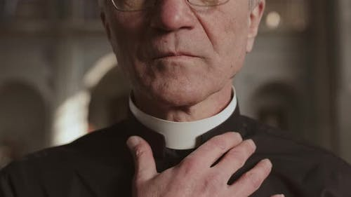 Aged Priest Fixing White Collar on His Neck