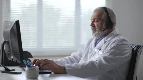 Male Doctor Sitting At The Table And Using Laptop