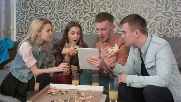 Cover Image for Group of Friends Eating Takeaway Pizza and Watching Programm on Tablet