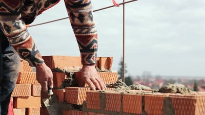 Close Up of a Man Building a Brick House