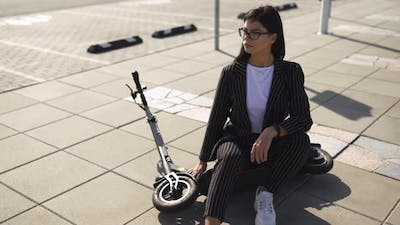 Young Woman in Business Suit Sitting on Escooter Near Mall