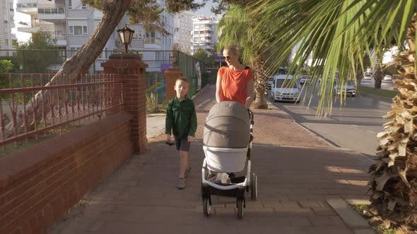 Thumbnail for A Woman Walking with a Baby Carriage and a Seven Years Old Son