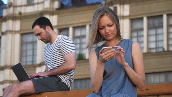 Thumbnail for Man using laptop and woman using smartphone sitting on