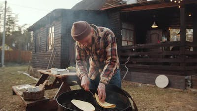Man Cooking Tortillas on BBQ Grill